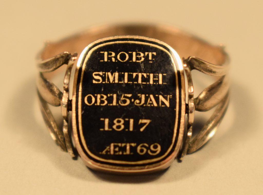 Photographie en couleur de la face d'une bague en or rose. La bague est de couleur or et l'élément décoratif est un détail au fond noir et aux lettres et bordures or avec l'inscription « ROBT SMITH OB 15 JAN 1817 AET 69 ». Le fond derrière et sous la bague est beige.