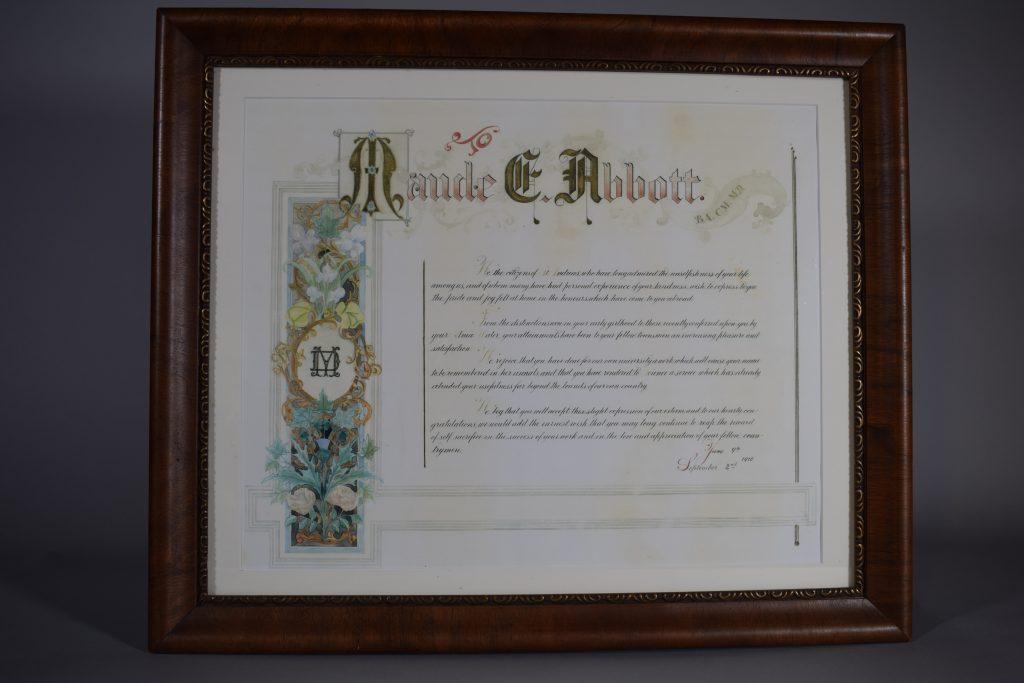 Certificat de reconnaissance en couleur. En haut, « Maude E. Abbott » dont les initiales sont en lettrines et dans une bannière à droite « B.A., C.M., M.D. ». Du côté gauche, une banderole avec des fleurs dans un encadré noir entoure un cercle doré avec les lettres « MD » superposées.