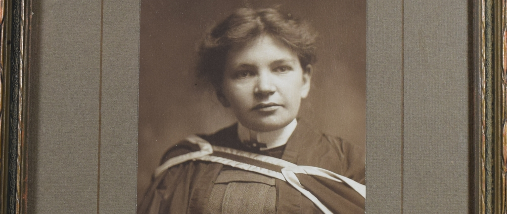 """Black and white photograph of Maude Abbott as a young adult, from the waist up. She is wearing a graduation gown. Her dark hair is tied behind her head and she is looking slightly to her left. There is a signature in the lower right corner, in ink: """"Sincerely Yours. Maude Elizabeth Seymour Abbott"""". The printer's signature appears below this: """"Rice. Montreal""""."""