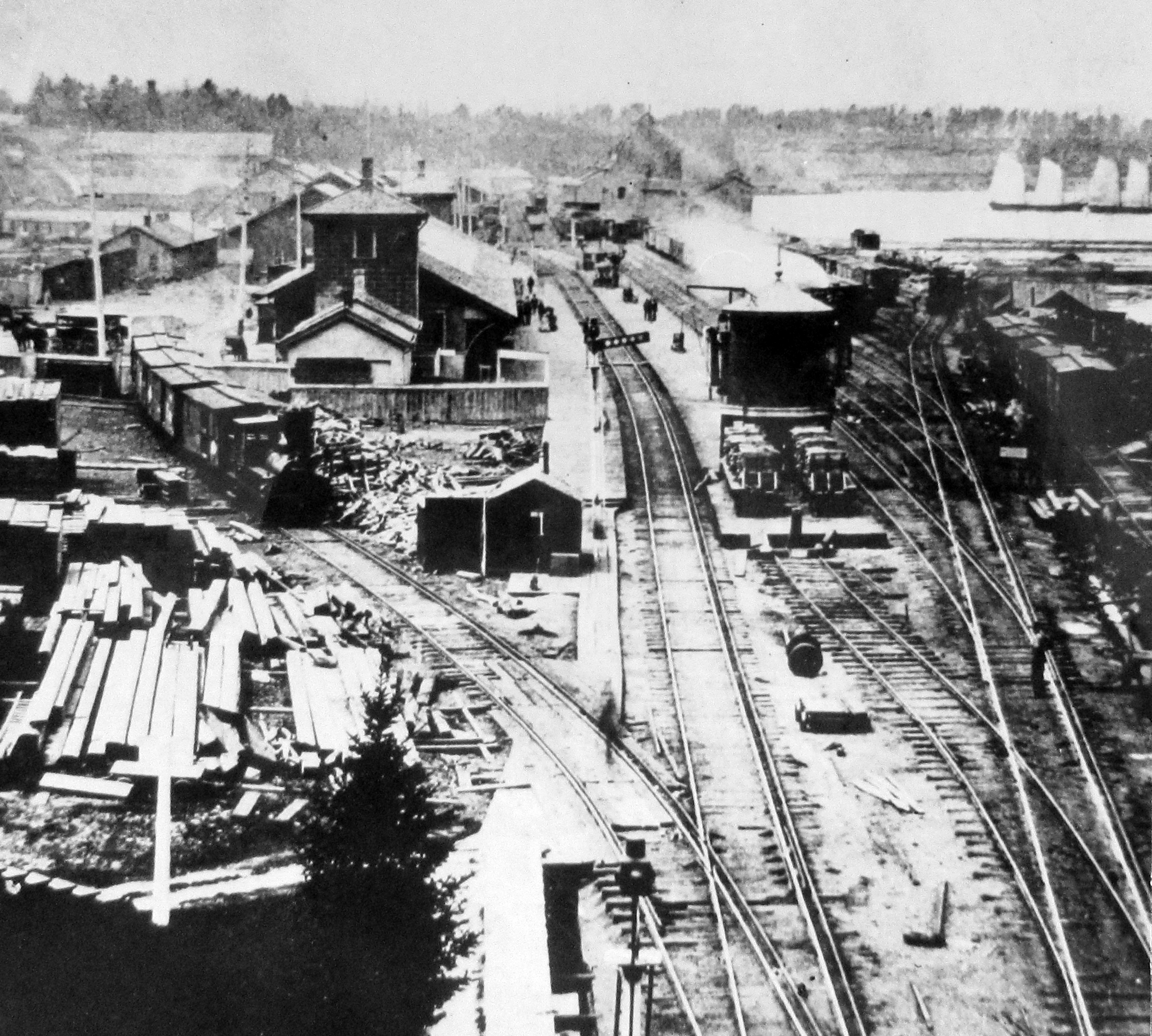 The Great Western Railway Yards and Station in which train cars lined up to one side of the station are visible. There are also piles of lumber and other materials lining the tracks. Two workers are visible in the foreground.