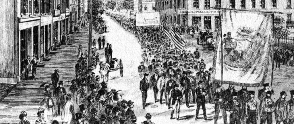 A cropped version of the cover of the Canadian Illustrated News from June 8 1872 depicts the parade of workers on May 15th 1872. There are dozens of spectators watching from the sidewalks as the parade of workers carry large banners and flags through the centre of the street.
