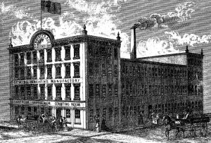 An illustration of R. M. Wanzer's three-storey factory with two four-storey buildings at each end. It takes up an entire city block and there is a flag at the front of the building and a tall chimney in the centre. People walk in front of the building and horse-drawn carriages drive past.