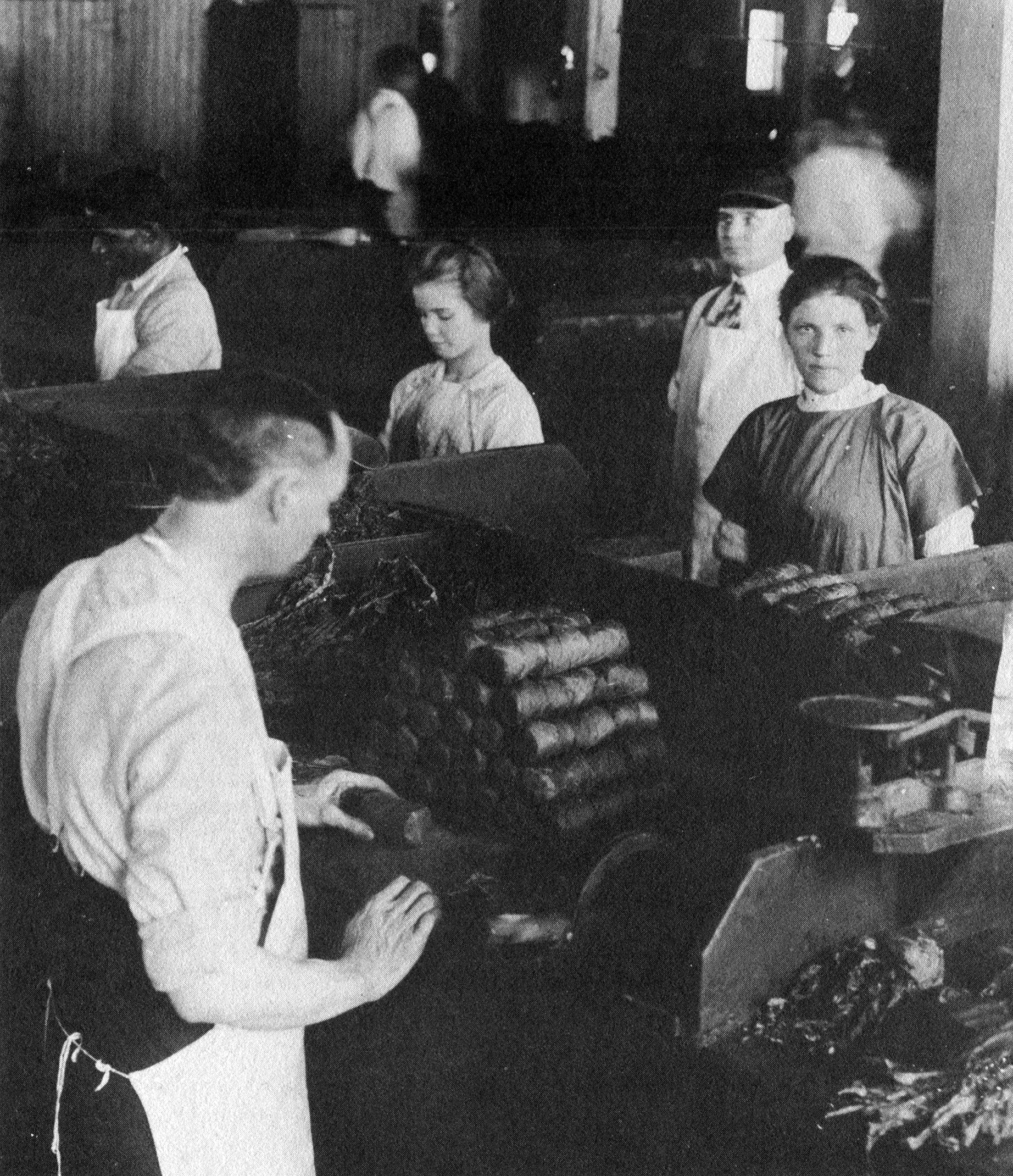 Young women and children working on the shop floor of Tuckett and Billings Tobacco Manufactory. The women are dressed in 19th century uniforms, with many wearing white work aprons. Rolls of tobacco sit in front of them and one young woman looks directly at the camera.