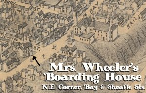 An illustrated map shows part of the city of Hamilton in the mid-1800s. Illustrated houses and other structures fill the map leading to a sloped hill on the right side of the image. A three-storey building at the North-East corner of Bay and Sheaffe Streets is identified as Mrs. Wheeler's Boarding House.