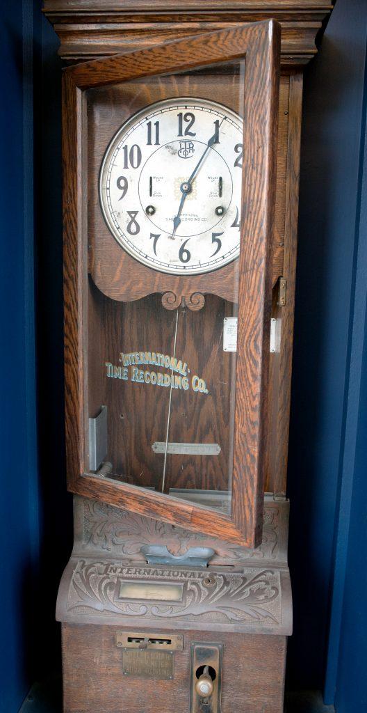Horloge murale en bois dotée de fentes pour billets et d'un levier horodateur. Le levier doit être décalé pour inscrire l'heure sur le bordereau, puis remis en position verticale.