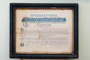 A photo of the International Typographical Union Charter from 1872. The signed paper charter uses historic calligraphy and has been preserved with glass and a wooden frame.