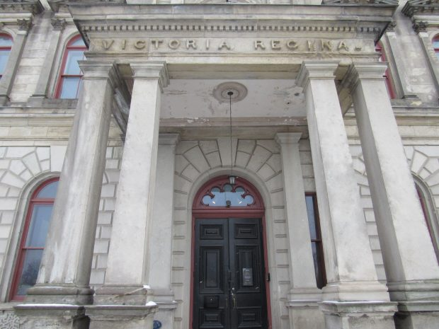 The entrance to a two-storey building. The door is framed by two pillars on each side and carved in the top of the portico entrance is the Latin Victoria Regina