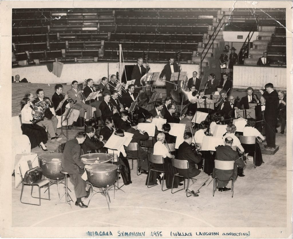 Wallace Laughton conducts the orchestra in a stadium