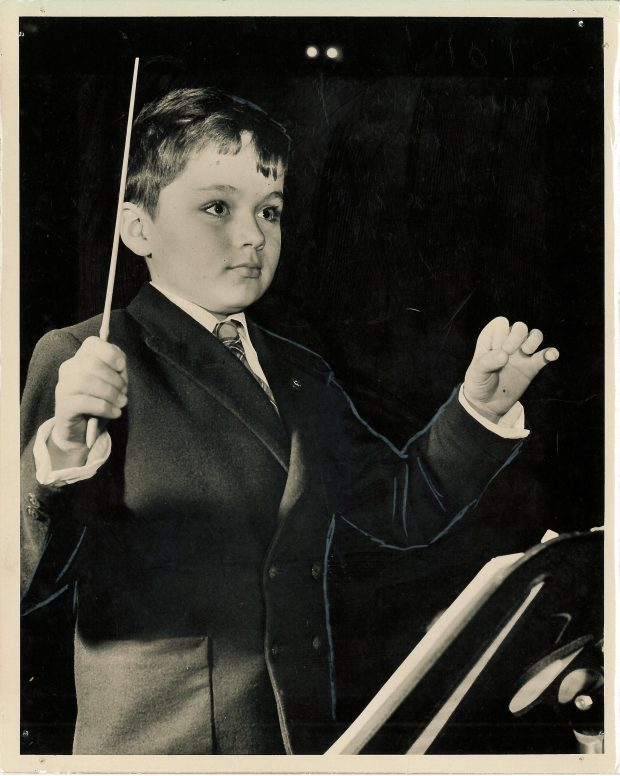 A young boy in a suit holds a conductor's baton in one hand and gestures with the other