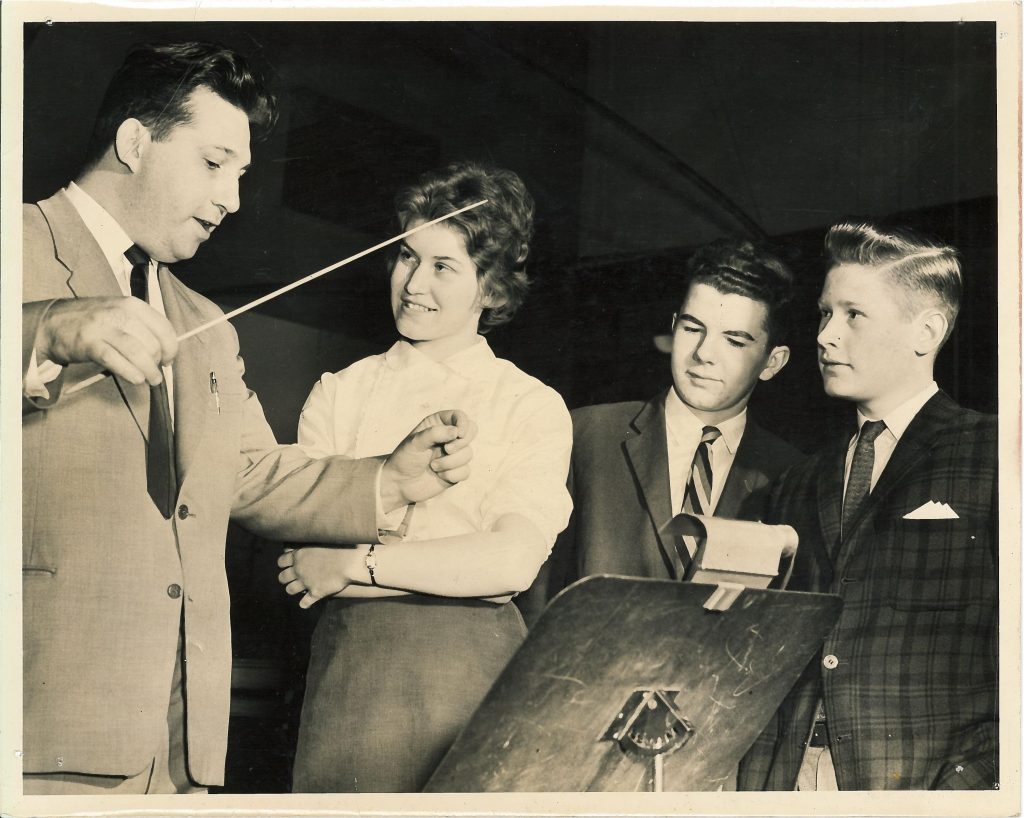 Leonard Pearlman demonstrates conducting to 3 students