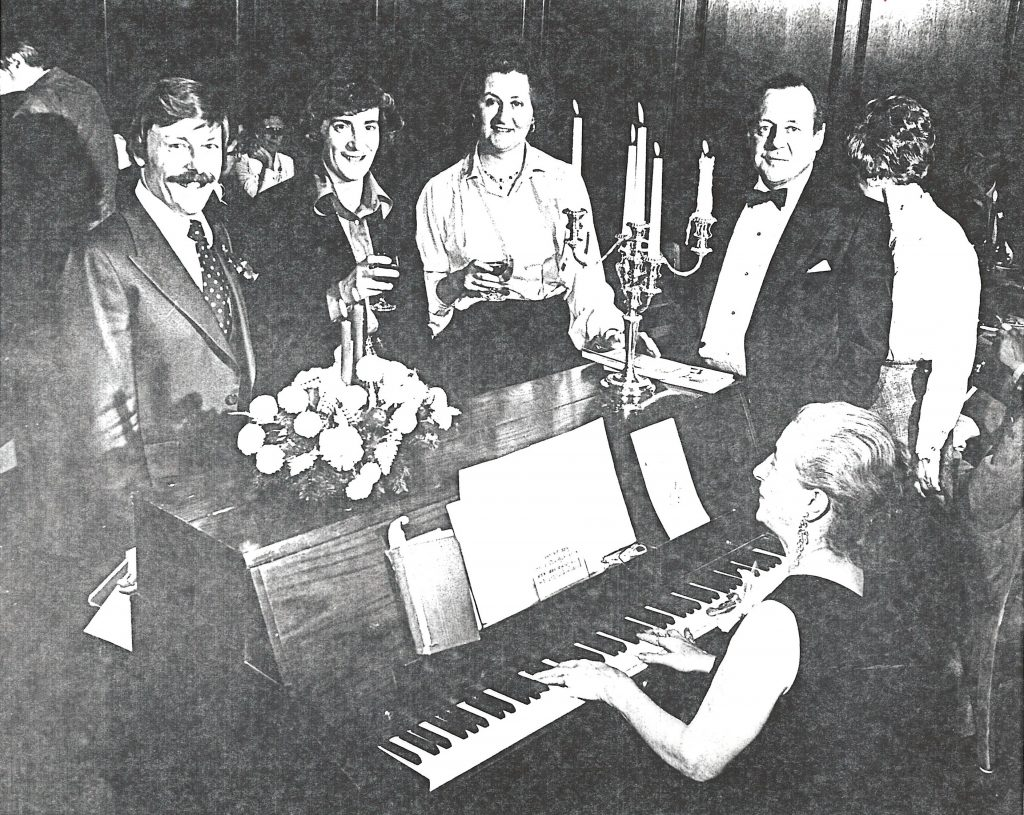 4 board members stand at piano during party