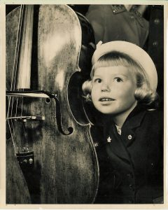 A young girl listens to a cello