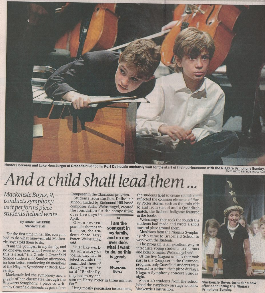 Two students sit at a xylophone on stage. Newspaper article titled