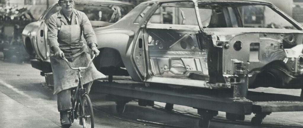 Black and white image of a man in an apron and a backwards baseball cap riding a bicycle alongside an unfinished car on an assembly line.