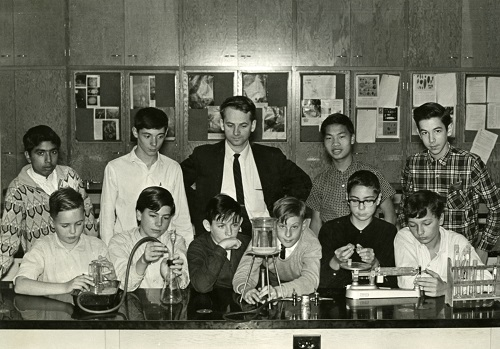 Graham Beard in the middle of two rows of students that are posing with scientific equipment. 1965
