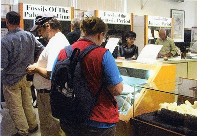 A group of people standing around, and looking down at, various museum displays.