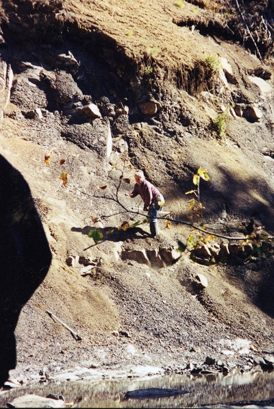 Graham Beard standing on steep riverbank in a fossil-bearing rock formation in the Comox Valley.