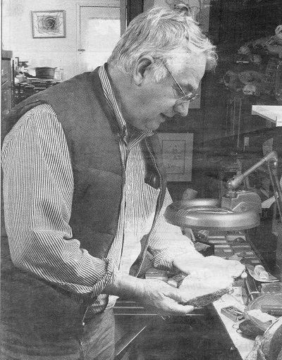 Graham Beard standing in his home, looking at a fossil under lamplight. c. 1995