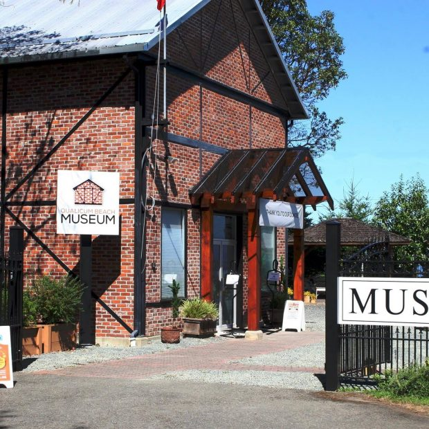 A two-storey building built of red bricks and black metal beams, photographed on a sunny day.