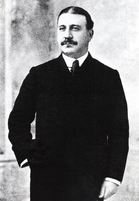 Standing portrait of Francis Clergue wearing a black suit and tie, his hand is in his pocket, his hair is parted down the middle, he has a big bushy moustache.