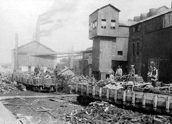 Supplies arriving by steam engine, debris in foreground, workers standing behind train cars.