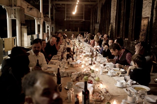 People dining at a long table upstairs at the Machine Shop