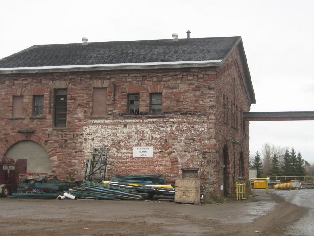 L'édifice en grès photographié un jour de grisaille avec un amoncellement de tuyaux d'acier en face du bâtiment.