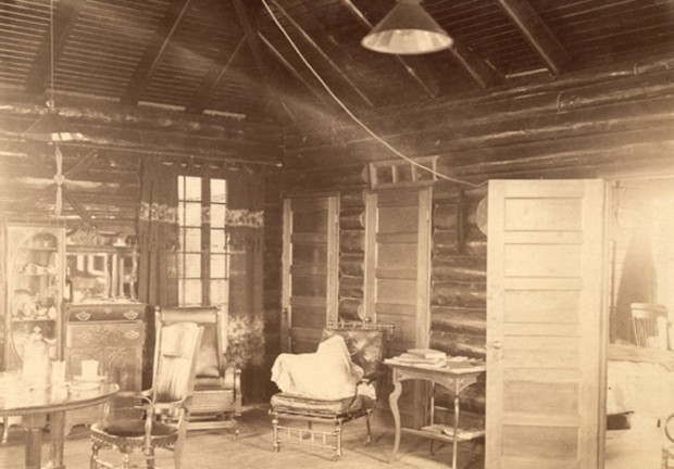 Blockhouse interior. Log cabin with ceiling lamp, one window, several chairs, a table and chest of drawers.