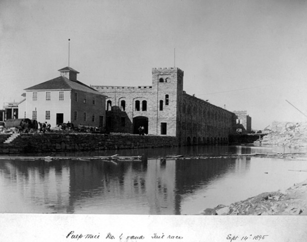 Image of the Pulp Mill No. 1 completed. The tall sandstone building is set back on the water.