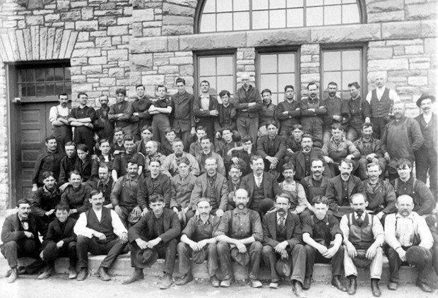 Black and white image of 61 men, sitting or standing in five rows, in front of a stone building.