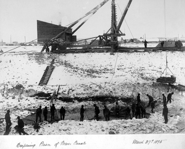 Men are seen digging a deep hole in the construction of the power canal. Snow on the ground.