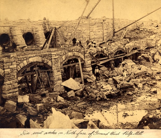Construction of sandstone arches. Busy scene with cranes, rocks and workers.