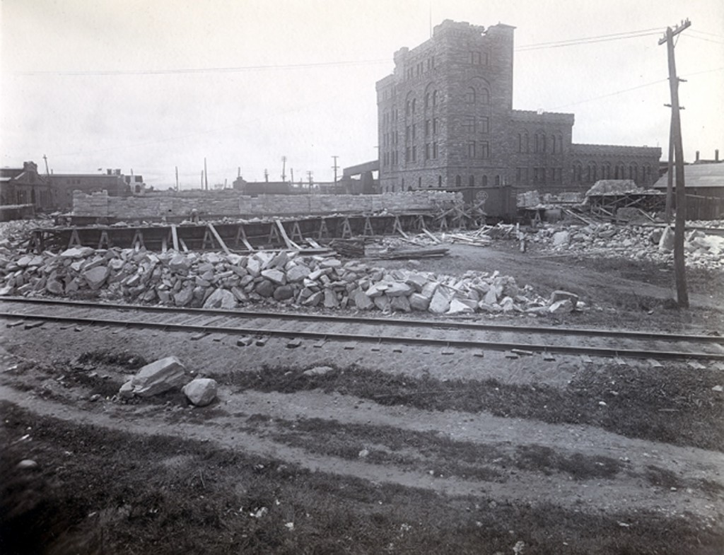 Rocks laying alongside of railway track, pulp tower in the background