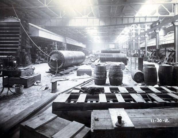 Paper mill warehouse, wooden barrels, crates, and paper rollers strewn across the floor.