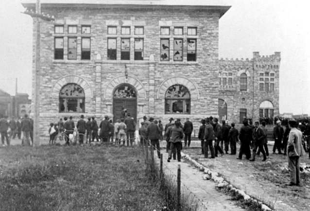 Rioting workers standing in front of sandstone building. The windows of the building have all been broken, presumably by angry rioters.