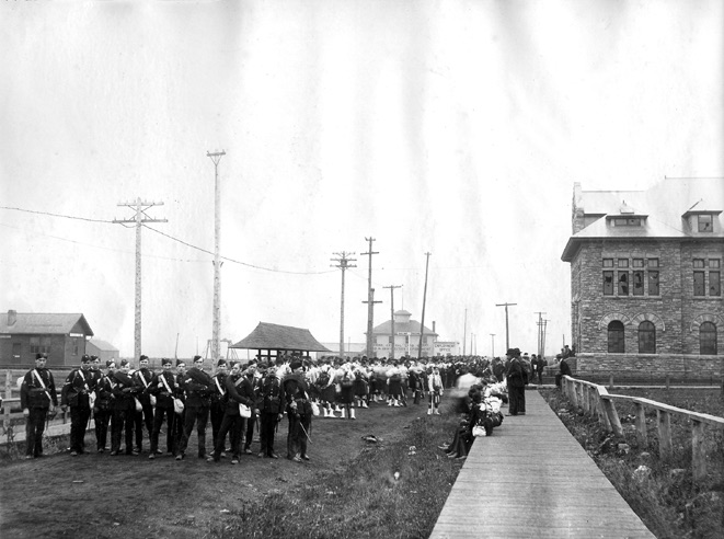 Soldiers standing to the left of the administrative building on a wooden sidewalk.