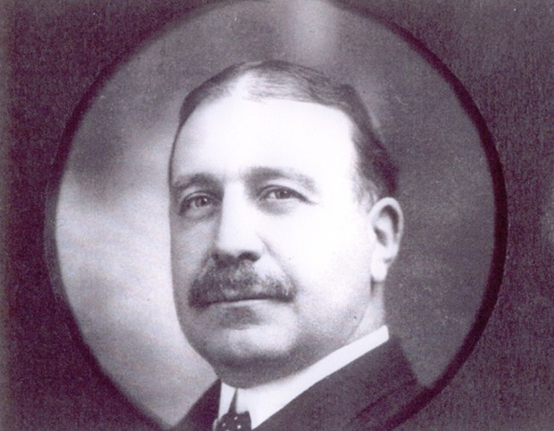 Clergue portrait in circular frame. Dark hair parted in the centre, large moustache. Black suit with white collar.
