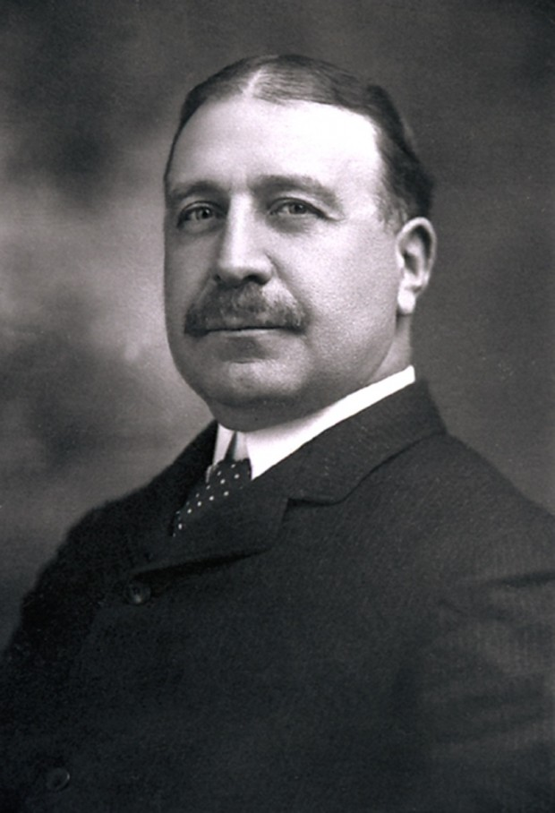 Black and white portrait of Francis Clergue. He wears a black suit and tie, has a moustache and his dark hair is parted in the middle.