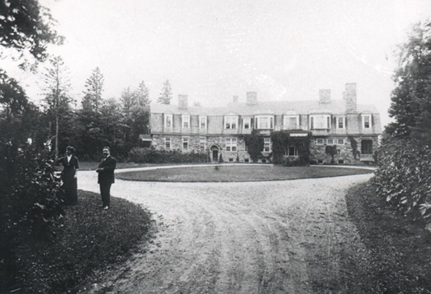 Circular drive way and lawn in front of stone mansion. Two people standing on lawn.