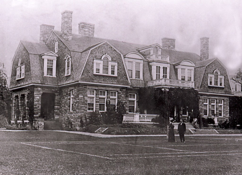 Two people standing on large lawn in front of stone mansion on a hill behind.