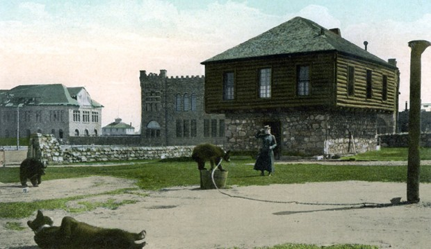 Postcard of the block house, bears chained in the yard, woman in dress walking out from the house. Machine Shop in the background.