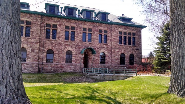 Exterior image of the administration building in summer. Three storey sandstone building, with arched windows on the first floor. Green grass in front and bridge/walkway over original Northwest Company canoe lock.