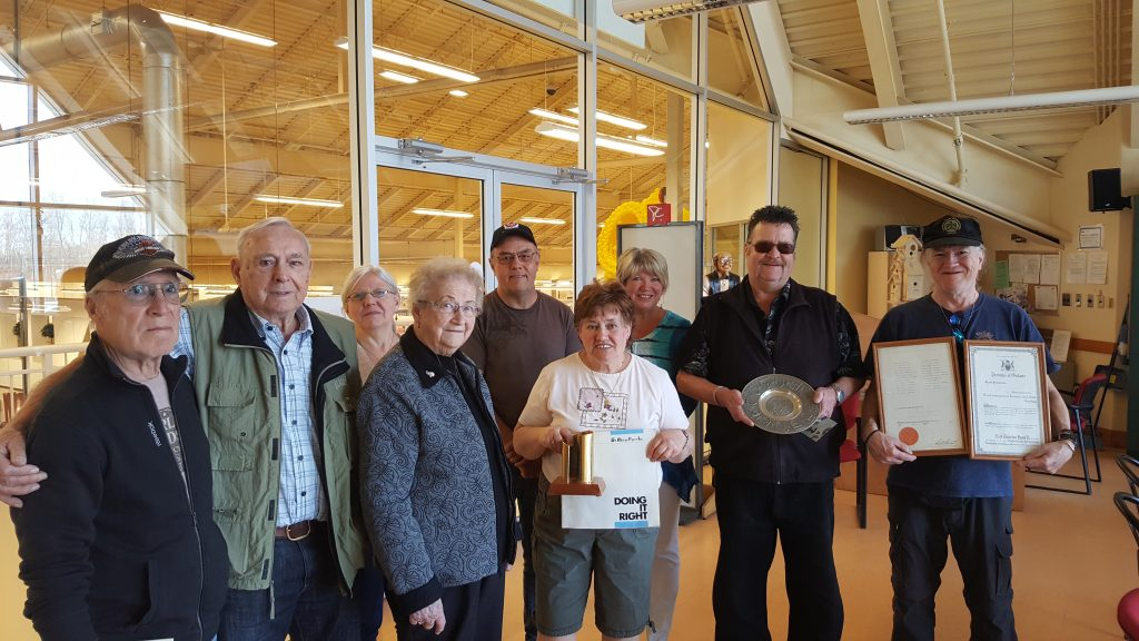 Former employees, predominately seniors, stand together holding paper mill artifacts they collected over the years. Nine people, men and women photographed.