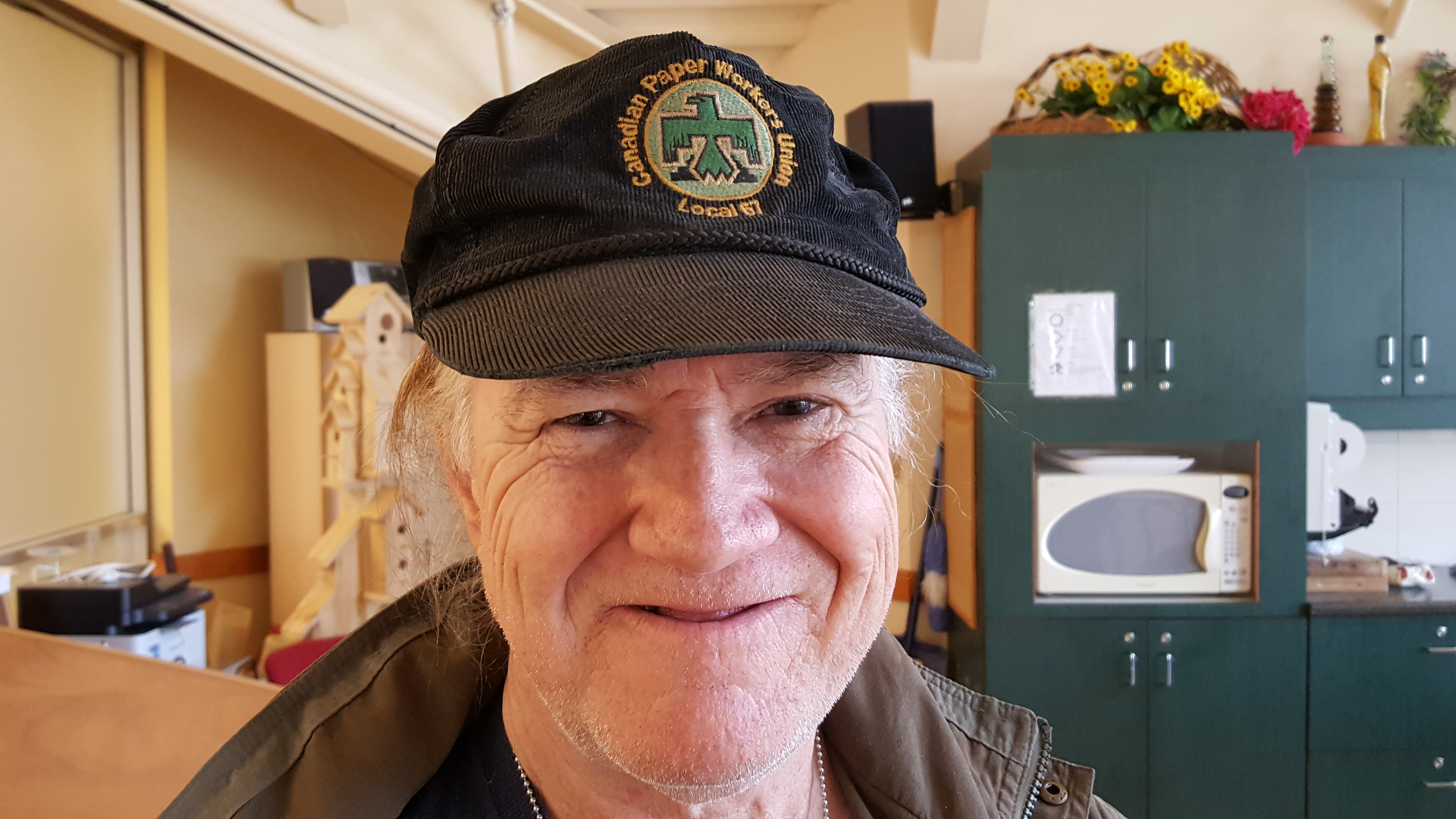"Retired paper mill worker wearing a Canadian Paper Workers Union ball cap. He has a toothless grin and is standing in the kitchen ""Upstairs at Rome's"" at the retirees meet-up."