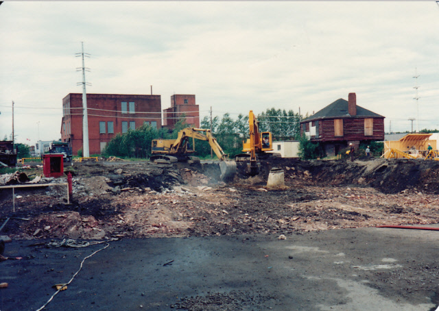 Cement in foreground, Clergue's block house is in the back right corner of the photo. Two excavators digging up ground in preparation for construction.