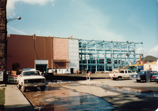 Blue steel beams erected on one side of the new building, the other side to the left is being covered with siding. Trucks are present, a sign leaning against the machine shop reads construction area.