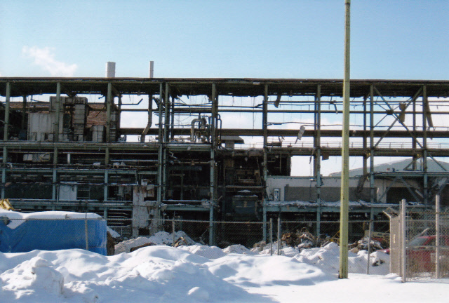 The bare beams of one of the modern buildings are exposed through demolition. There is snow in the foreground of the image. The building looks decrepit.