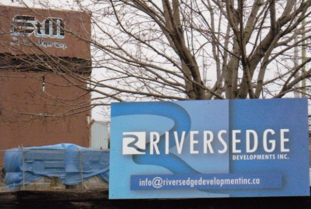 Photograph of the Riversedge Developments Inc. sign mounted on the fence of the St. Mary's Paper Corp. property.