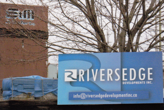 Photo de l'enseigne de Riversedge Developments Inc. sur la clôture de la propriété de la St. Mary's Paper Corp.