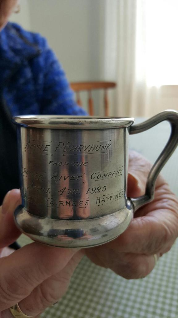 Two elderly hands holding a small silver mug with an engraving to Annie Pohrybunk, April 4, 1925 from the Spanish River Company.